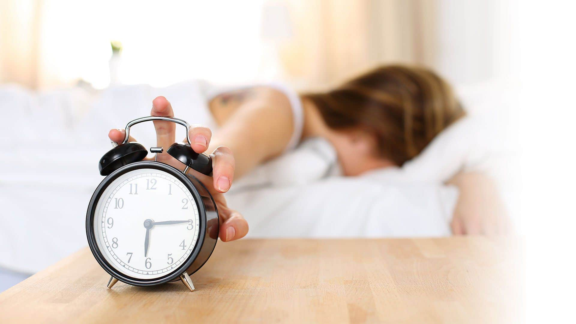 woman reaching for her alarm clock in the morning