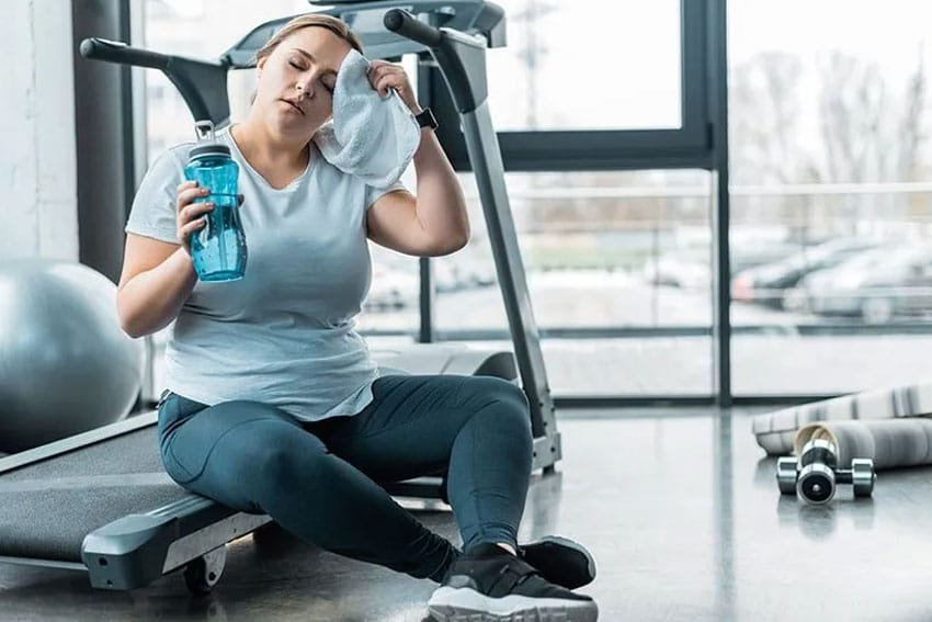 Woman taking a break after working out on the treadmill at the gym