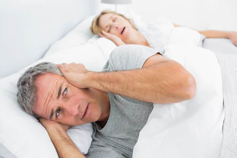 Annoyed man holds his hands over his ears while wife snores next to him