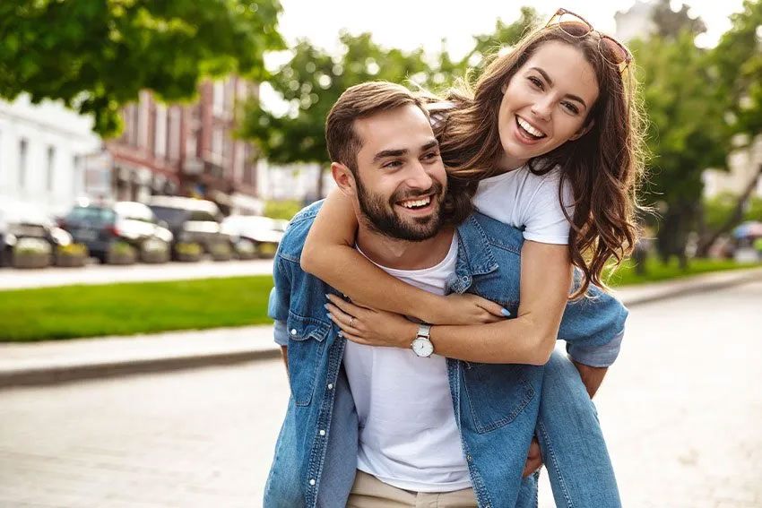 man giving his girlfriend a piggyback ride while walking outside