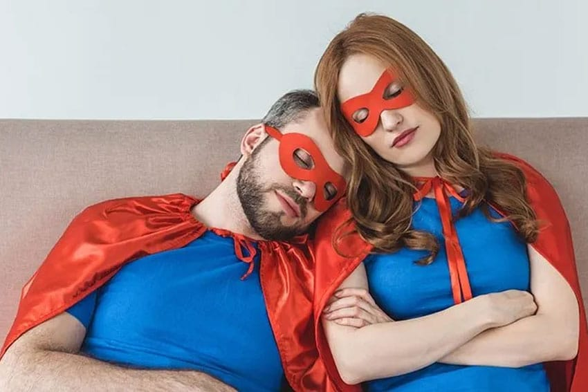 Superhero parents take a moment to rest on a couch