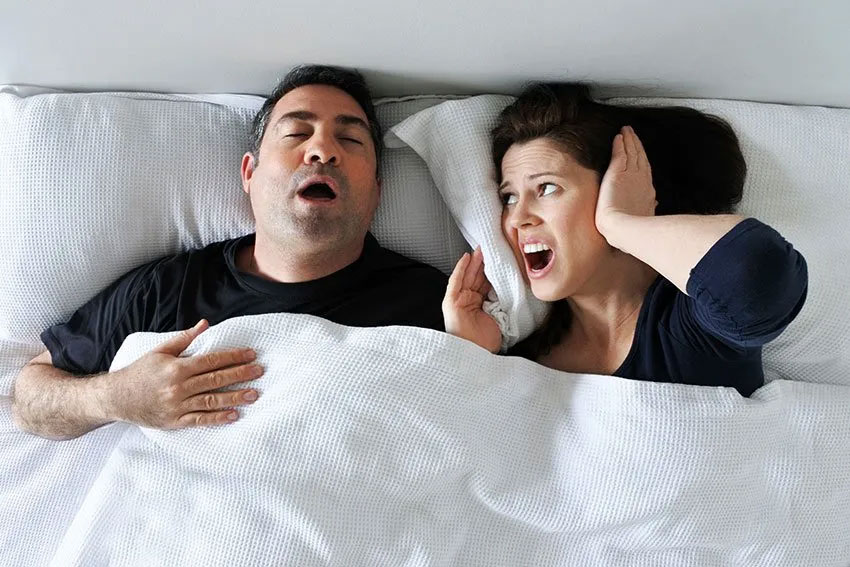 Angry woman holds pillow over her ears while husband lays next to her snoring