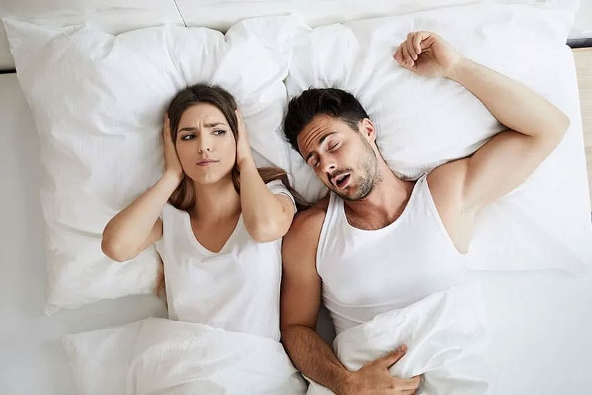 Young woman covers her ears while husband snores loudly next to her in bed