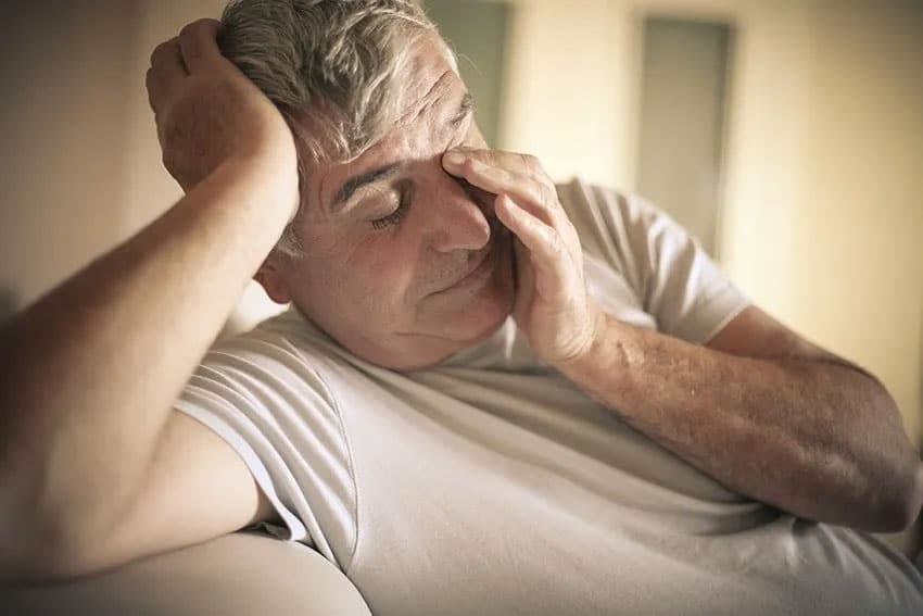 Older gentleman tired, rubbing his eyes