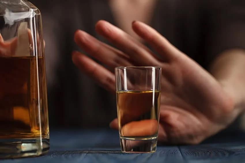 A female hand pushing away a shot at a bar