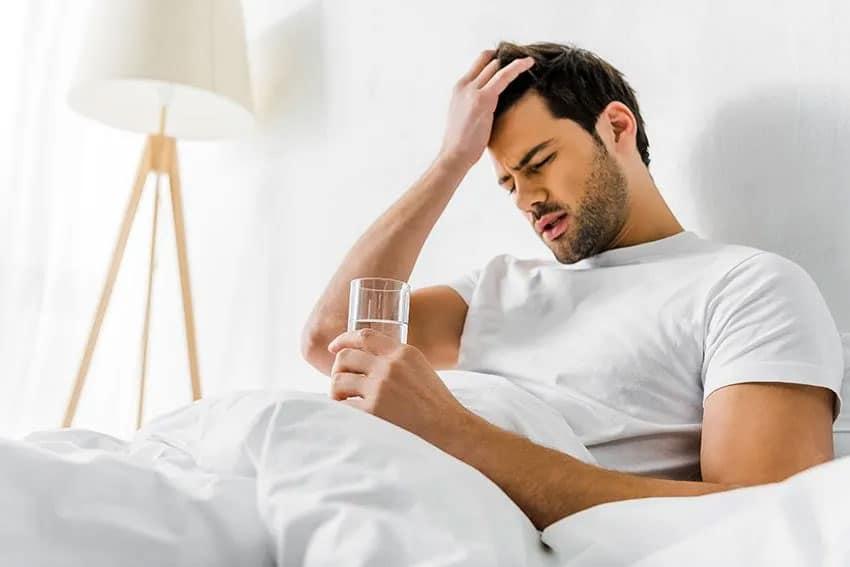 A man having a morning headache drinks water