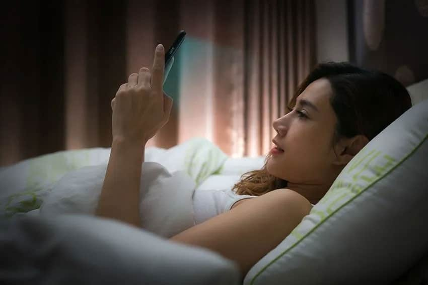 A young woman typing on her phone while laying in bed