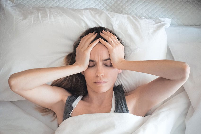 young woman waking up in bed with a headache
